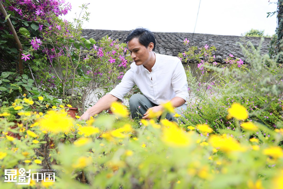 罗名华正在打理酒吧前面的小花园。新华网 王晓震摄